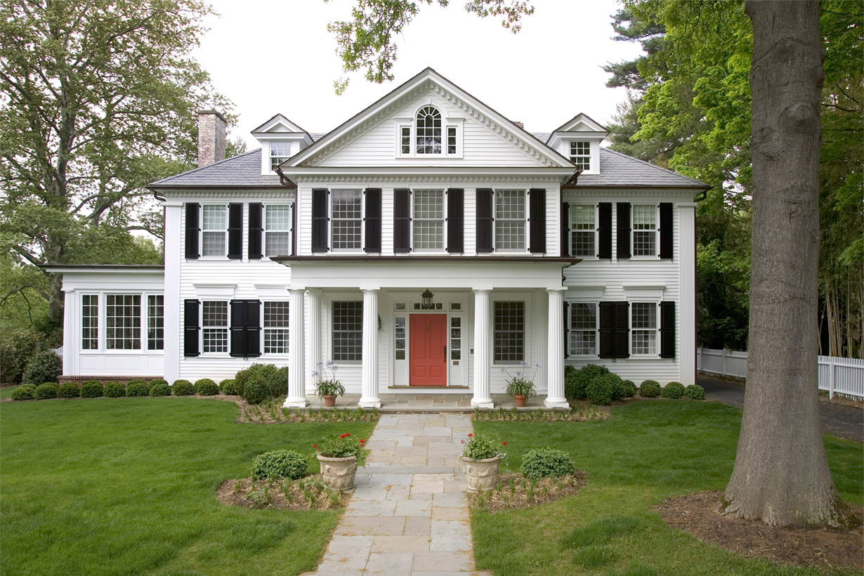 A white, two-story home representing home renovations by building company Lasley Brahaney Architecture + Construction in Princeton, NJ