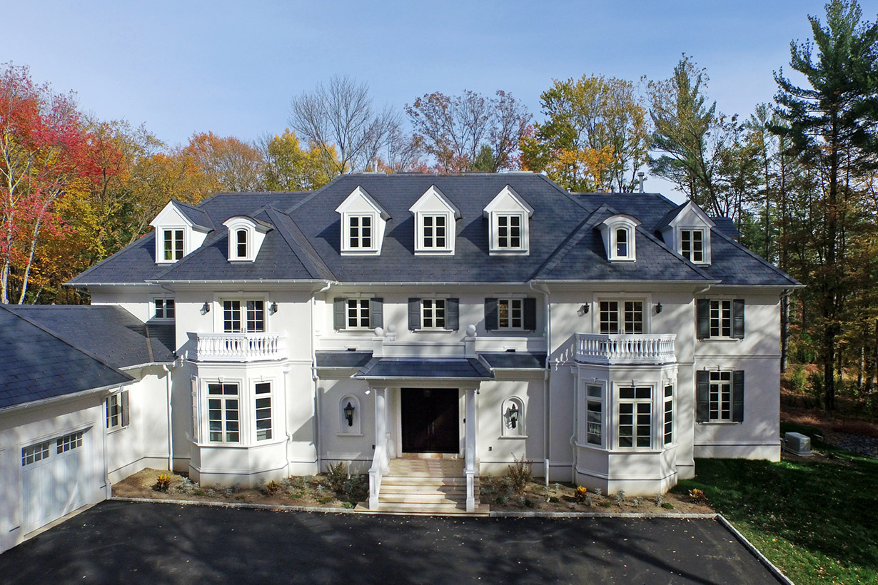 White and grey two-story home with garage representing work by building company Lasley Brahaney Architecture + Construction in Princeton, NJ