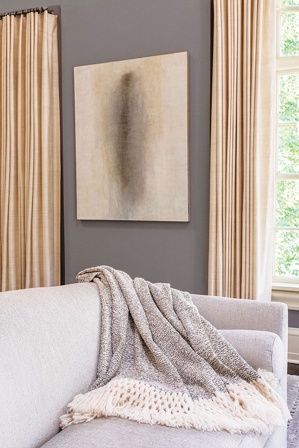 NEUTRAL TONES | A hand-woven salt-and-pepper Peruvian throw with oversized fringe echoes the soft natural tones in the atmospheric oil painting by New York City artist Louise Crandell.