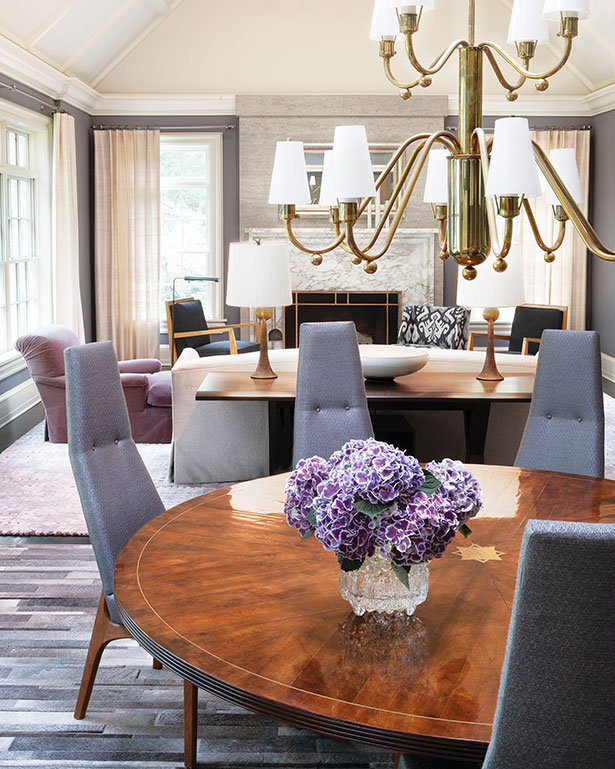 Vintage dining room chairs by Adrian Pearsall, newly upholstered in silver metallic fabric, surround a high-cut mahogany marquetry table that has a centered brass star fillet and expands to seat 12.