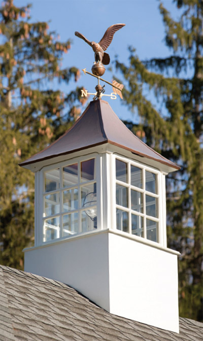 The cupola on the garage features a copper top with a weathervane.