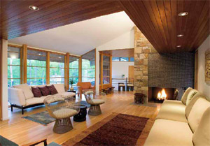 Seating of all sorts in the upper-level living room is framed by quarter-sawn white oak flooring (with hydronic radiant heat), clear-finish tongue-and-groove cedar soffit beams with recessed lights, view-loving windows, and a fireplace where wood, raw stone, a slate hearth, and glass tile meet seamlessly. Light also floods in from the clerestory above. The furnishings are part of the homeowners' collection of historical and classic furniture, art, and African textiles and artifacts.