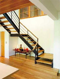 A steel beam buried in a wall secures a floating staircase from the foyer above. Open risers and oak-capped railings enhance the flow. White oak seems to spill down the stairs to the cedar-accented dining room and become another expanse of continuous flooring. The narrow door opens to a powder room.