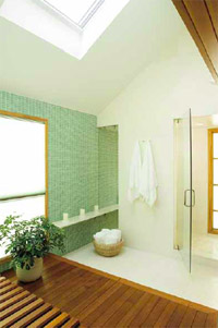 Wood, glass, and stone come together again in the master bathroom in the back of the house on the lower level. Limestone covers the floor and lines the shower chamber, which also features a frameless door and frosted-glass exterior window. The soft green glass-tile accent wall showcases the cedar platform, bench, and soaking tub (not shown); surrounding windows look into an enclosed garden outside. Two skylights let in the light.
